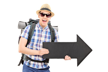 Excited male tourist holding a black arrow pointing right