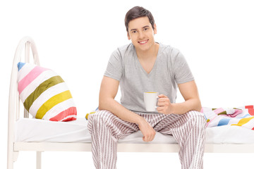 Guy drinking a coffee seated on a bed