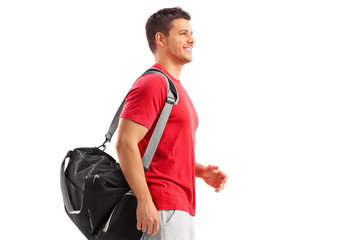 Male athlete walking with a sport bag