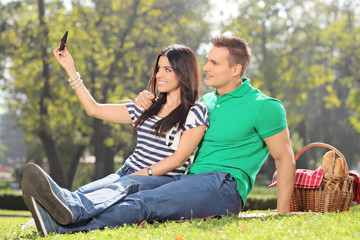 Girl taking a selfie with her boyfriend in park
