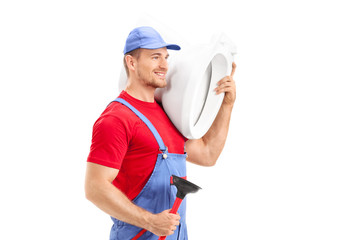 Male plumber carrying a toilet and holding a plunger