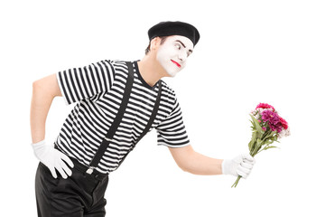 Mime artist giving flowers to someone