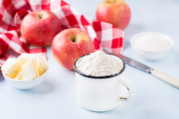 Cup of flour, butter, red apples and sugar