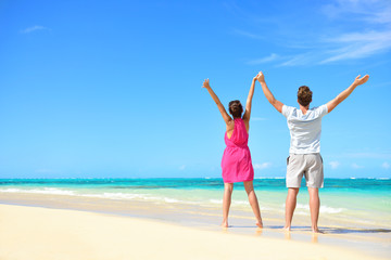 Happy free couple cheering on beach travel holiday