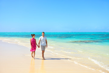 Summer vacation couple walking on beach landscape