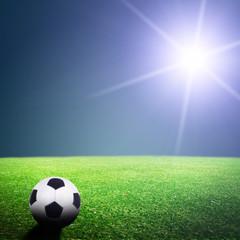 Shiny soccer ball in full stadium lights at night