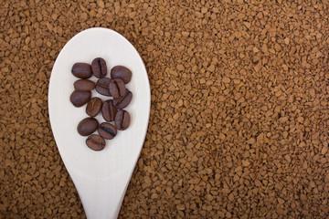 Целые зерна кофе на фоне растворимого кофе