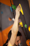 Rock climber on artificial climbing wall, hand in focus