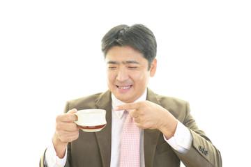 コーヒーを飲む笑顔のサラリーマン