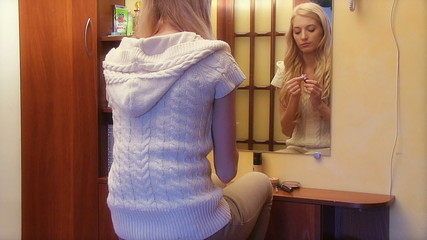 Beautiful girl looking in the mirror and applying cosmetic