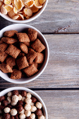 Various sweet cereals in ceramic bowls on wooden background