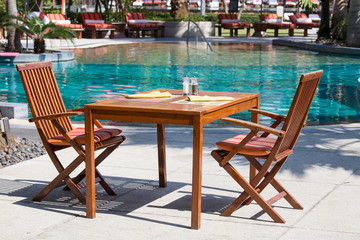 Table and chairs in empty cafe next to the pool. Thailand