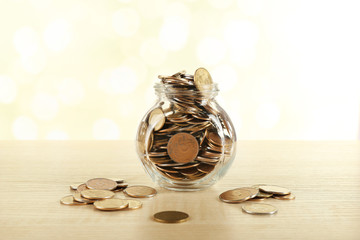 Gold coins in glass bottle on bright blurred background