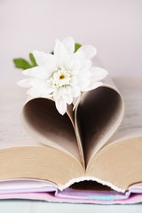 Open book with shape of heart from pages and flower