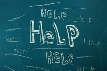 Help written with chalk on blackboard