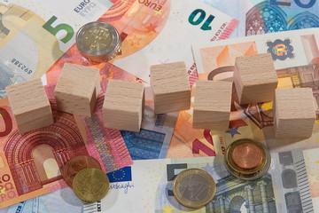 Geldscheine liegend Holzwürfel Münzen