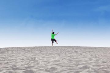 Cheerful little boy jump on desert
