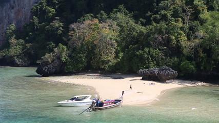 motor speed boat tied up at rocky island coast