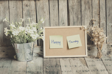 Vintage style effect Happy Thursday message on corkboard with fl
