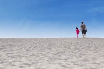 Girl with her father walk on desert