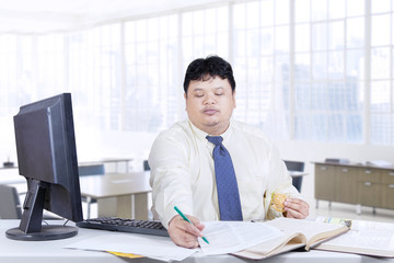 Male manager writes on paper in office