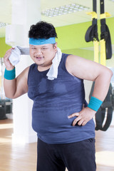Obesity person wiping his sweat at gym