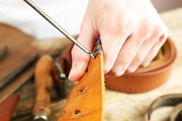 Repairing leather belt in workshop