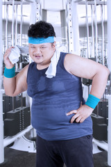 Overweight person cleaning sweat at gym