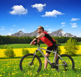 Cyclist with the mountain bike in spring landscape