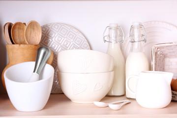 Kitchen utensils and tableware on shelf