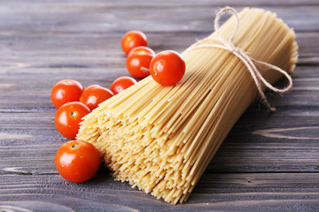 Raw pasta and tomatoes on wooden background