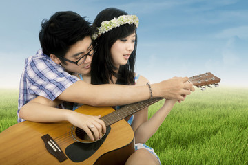 Romantic couple playing guitar at field