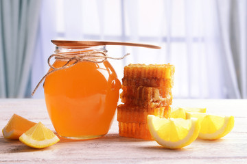 Delicious honey with lemon on table on light background