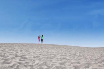 Two kids jump on desert