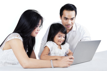 Two parents teaching their daughter with laptop
