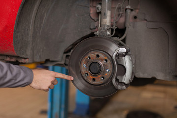 Hand pointing at car brake disc