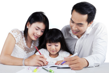 Young family studying together on table