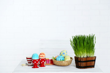 Table with fresh grass, decorated Easter eggs and brushes,