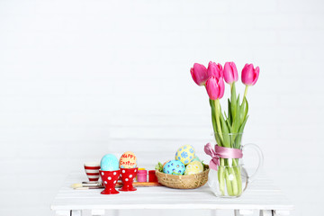 Table with flowers, decorated Easter eggs and brushes,