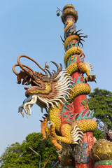 dragon statue climb the pole with sky background