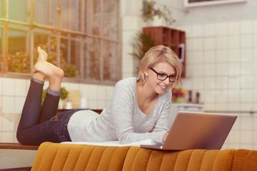 lächelnde frau mit brille schaut auf ihren laptop