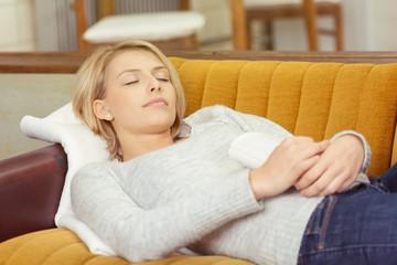 blonde frau liegt schlafend auf dem sofa