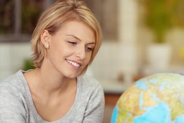 lächelnde junge frau schaut auf globus