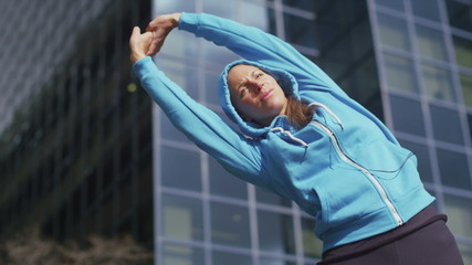 Young woman in the city warming up before a run in slow motion