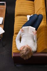 frau liegt auf dem sofa und liest ein buch