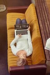 junge frau liegt auf dem sofa und surft im internet