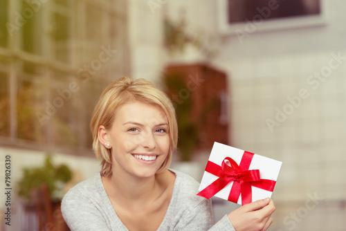 lächelnde junge frau mit einem gutschein - 79826330
