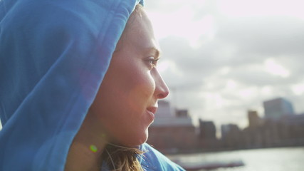 Young woman in a hood looks out to the river in slow motion