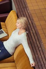 müde frau mit laptop macht eine pause auf dem sofa