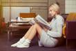 Leinwanddruck Bild - entspannte junge frau liest die tageszeitung